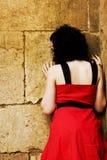 Droevige vrouw tegen muur Royalty-vrije Stock Foto's