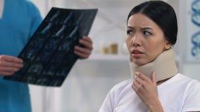 Droevige vrouwelijke patiënt die ongemakkelijk in cervicale kraag, artsenonderzoek voelen stock footage