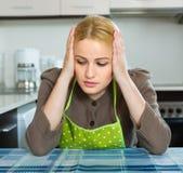 Droevige vrouwenzitting bij keuken Stock Fotografie