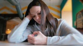 Droevige vrouwenzitting in een koffie en wachten haar orde en het kijken haar vingers close-up stock footage