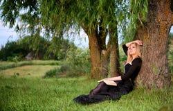 Droevige vrouwenzitting onder een boom stock foto's