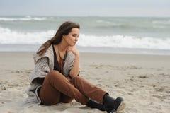 Droevige vrouwenzitting op een overzees strand Stock Foto