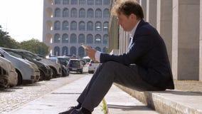 Droevige wanhopige bedrijfsmens die op de telefoonzitting op straat beginnen te schreeuwen stock videobeelden