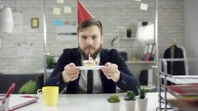 Droevige zakenman die een eenzame verjaardag in het bureau vieren, blaast hij een kaars op een kleine cake Probeer cupcakes, cake stock video