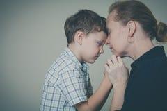 Droevige zoon die zijn moeder thuis koesteren stock foto's