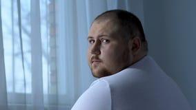 Droevige zwaarlijvige mens die camera hopeloos bekijken, depressie veroorzaakt gezondheidsprobleem stock footage