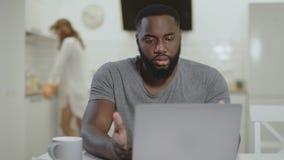 Droevige zwarte mensen werkende laptop bij open keuken Gek jong kerel het typen notitieboekje stock footage