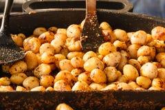 Drog tillbaka unga potatisar med kryddor i bunke Arkivbild