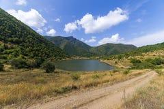 Droga blisko jeziora na montains tle Zdjęcie Royalty Free