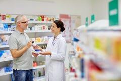 Droga de compra do farmacêutico e do homem superior na farmácia Fotografia de Stock