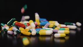 Droga farmacêutica, um grupo de cápsulas redondas multi-coloridas das tabuletas com medicina antibiótica nos pacotes doença filme