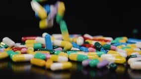 Droga farmacêutica, um grupo de cápsulas redondas multi-coloridas das tabuletas com medicina antibiótica nos pacotes doença video estoque