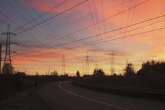 Droga i linie energetyczne na tle zmierzchu niebo Zdjęcia Stock