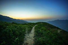 Droga na kręgosłupie i wierzchołek góry zakrywać z greenery z delikatnymi dolinami przy świtem zdjęcia stock