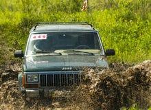 Droga pojazdu gatunku dżip Cherokee pokonuje jamę błoto Zdjęcia Stock