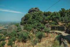 Droga przemian na wzgórzu zakrywającym drzewami i skałami blisko Monsanto zdjęcia royalty free