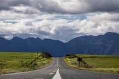 Droga przez rolniczych poly z pasmem górskim w odległości - Somerset Zachodni, Zachodni przylądek, Południowa Afryka zdjęcia stock