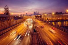 Droga przy nocą z światłami od wiele samochodów na tle metropolia obrazy royalty free