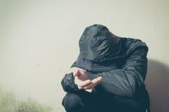 Droga sin hogar del hombre del mendigo y adicto al alcohol que se sienta solamente y deprimido en la calle en la ropa del inviern imagen de archivo libre de regalías
