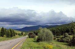 Droga w lesie pod niebieskim niebem z bielem chmurnieje Sayan góry Syberia Rosja Zdjęcie Stock