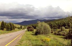 Droga w lesie pod niebieskim niebem z bielem chmurnieje Sayan góry Syberia Rosja Zdjęcia Stock