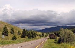 Droga w lesie pod niebieskim niebem z bielem chmurnieje Sayan góry Syberia Rosja Obrazy Stock