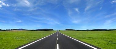 Droga w przodzie z ocechowaniami chmury na stronach pole obraz stock
