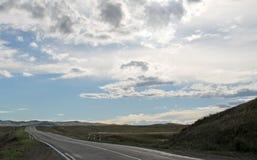 Droga w stepie pod niebieskim niebem z bielem chmurnieje Sayan góry Syberia Rosja Fotografia Royalty Free