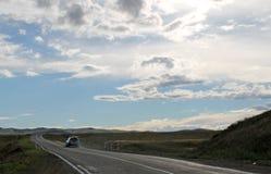 Droga w stepie pod niebieskim niebem z bielem chmurnieje Sayan góry Syberia Rosja Zdjęcia Stock