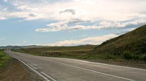 Droga w stepie pod niebieskim niebem z bielem chmurnieje Sayan góry Syberia Rosja Obrazy Stock