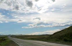 Droga w stepie pod niebieskim niebem z bielem chmurnieje Sayan góry Syberia Rosja Fotografia Stock