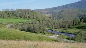 Droga wzdłuż rzeki lokalizować między zielonymi wzgórzami zbiory