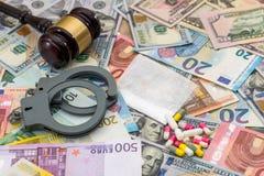 Droga y sustancias prohibidas con las esposas en dólar y euro Fotografía de archivo