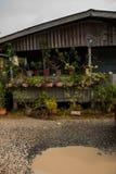 Droga z kałużami w wiosce Dom z kwiatami w garnkach Malezja, Borneo, Sabah obraz stock