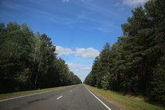 Droga z ocechowaniem wśród niebieskiego nieba i lasu zdjęcia stock