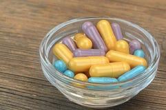 Drogas coloridas no recipiente de vidro pequeno no fundo de madeira imagens de stock
