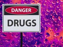 Drogas do perigo do sinal e gota de néon no vidro foto de stock