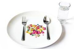 Drogas en un plato con la cuchara y la bifurcación imagen de archivo