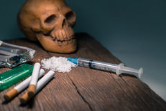 Drogas y cráneo en el piso de madera viejo Foto de archivo libre de regalías