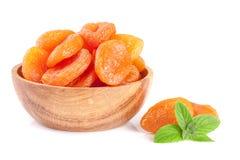 Droge abrikozen in een houten die kom met muntbladeren op witte achtergrond worden geïsoleerd Stock Foto