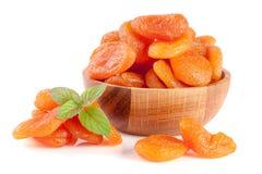 Droge abrikozen in een houten die kom met muntbladeren op witte achtergrond worden geïsoleerd Stock Afbeeldingen