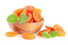 Droge abrikozen in een houten die kom met muntbladeren op witte achtergrond worden geïsoleerd Stock Afbeelding