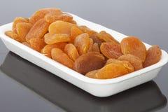 Droge abrikozen in een witte container Stock Fotografie