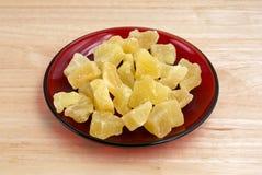 Droge ananasbrokken op rode plaat Royalty-vrije Stock Fotografie