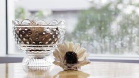 Droge bloem op lijst met een glas van droge bloemen en regenende achtergrond stock video