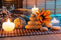 Droge bloemen, witte stenen, kaarsen op bamboemat Royalty-vrije Stock Fotografie