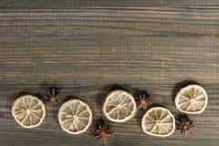 Droge citroenplakken met steranijsplant op houten lijst Stock Fotografie