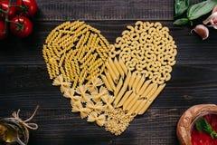 Droge deegwaren in de hoogste mening van de hartvorm Deegwaren en groenten op de donkere houten lijst Stock Afbeelding
