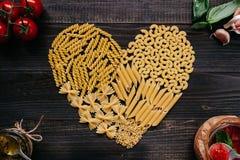 Droge deegwaren in de hoogste mening van de hartvorm Deegwaren en groenten op de donkere houten lijst Stock Fotografie