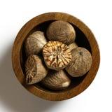 Droge geheel en besnoeiing nutmegs in donkere houten die kom op wit wordt geïsoleerd stock foto